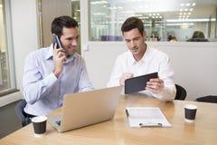 2 вскользь бизнесмена работая совместно в современном офисе с Ла Стоковое Изображение RF