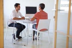 Вскользь бизнесмены говоря на столе и усмехаться Стоковые Фото