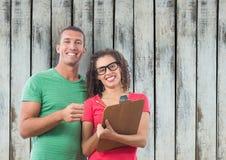 Вскользь бизнесмены с доской сзажимом для бумаги против деревянной стены Стоковое Фото