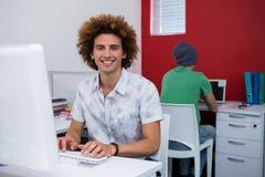 Вскользь бизнесмен используя компьютер в офисе Стоковая Фотография