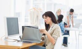 Вскользь женщина работая на столе с коллегами позади в офисе Стоковые Изображения RF