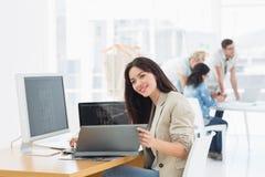 Вскользь женщина работая на столе с коллегами позади в офисе Стоковая Фотография RF