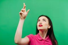 Вскользь женщина смотря вверх - изолированный над зеленой предпосылкой стоковое фото rf
