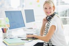 Вскользь женщина с шлемофоном на столе компьютера в офисе Стоковые Фото