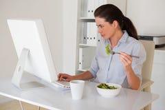 Вскользь коммерсантка брюнет есть салат на ее столе Стоковые Фотографии RF