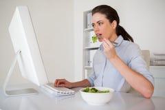 Вскользь коммерсантка брюнет есть салат на ее столе Стоковое фото RF
