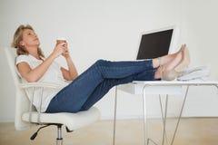 Вскользь коммерсантка имея кофе с ее ногами вверх на столе Стоковые Изображения