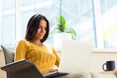 Вскользь коммерсантка сидя на стуле офиса с компьтер-книжкой Стоковое Фото