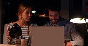 Вскользь коллеги используя компьтер-книжку и камеру на ноче акции видеоматериалы