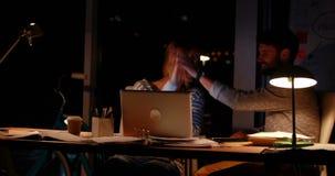 Вскользь коллеги используя компьтер-книжку на ноче сток-видео