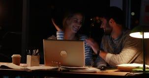 Вскользь коллеги используя компьтер-книжку на ноче акции видеоматериалы