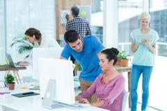 Вскользь коллеги используя компьютер в офисе Стоковое Фото