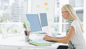 Вскользь молодая женщина используя компьютер в офисе Стоковые Изображения RF
