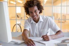 Вскользь молодое сочинительство бизнесмена на его столе усмехаясь на камере Стоковое Изображение