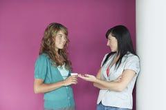 Вскользь молодые женщины говоря розовой стеной Стоковые Изображения RF