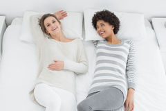 2 вскользь молодых женских друз лежа в кровати Стоковая Фотография