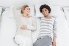 2 вскользь молодых женских друз лежа в кровати Стоковое Фото