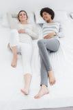 2 вскользь молодых женских друз лежа в кровати Стоковые Изображения