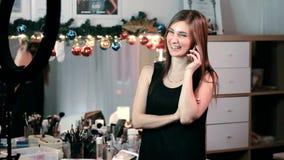 Вскользь одетая молодая профессиональная женщина принимает звонок в неофициальном но занятом современном офисе сток-видео