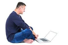 Вскользь одетая середина постарела человек сидя с компьтер-книжкой Стоковые Фотографии RF