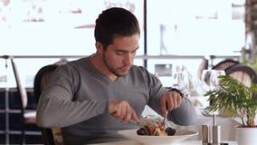 Вскользь одетый человек ест салат видеоматериал