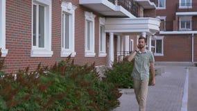 Вскользь одетый человек идя на улицу и говоря замедленным движением smartphone сток-видео