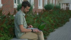 Вскользь одетый человек независимый сидит на стенде и использует его smartwatch и компьтер-книжку видеоматериал