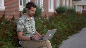 Вскользь одетый человек независимый сидит на стенде и использует его компьтер-книжку видеоматериал