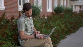 Вскользь одетый человек независимый сидит на стенде и использует его smartwatch и компьтер-книжку сток-видео