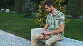 Вскользь одетый человек сидит на стенде в парке и использует его современный умный вахту сток-видео