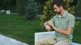 Вскользь одетый человек сидит на стенде в парке и использует его современный умный вахту акции видеоматериалы