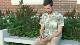 Вскользь одетый человек сидит на стенде и использует его smartphone видеоматериал