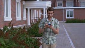 Вскользь одетый человек с прогулкой smartwatch на улице и использует его smartphone сток-видео