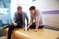 2 вскользь одетых молодого человека используя цифровую таблетку Стоковые Фотографии RF