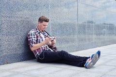 Вскользь парень смотря фото в камере пока отдыхающ outdoors внутри Стоковое Изображение RF