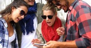 Вскользь друзья нося солнечные очки и используя smartphone сток-видео