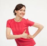 Вскользь усмехаясь молодая женщина показывая большие пальцы руки поднимает знак стоковая фотография