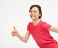 Вскользь усмехаясь молодая женщина показывая большие пальцы руки поднимает знак стоковое изображение rf