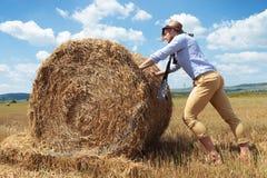 Вскользь человек напольный нажимающ стог сена Стоковая Фотография