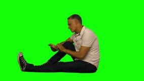 Вскользь человек сидя и отправляя СМС на телефоне сток-видео