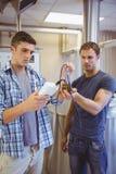 2 вскользь люд испытывая пиво в beaker Стоковое Изображение RF