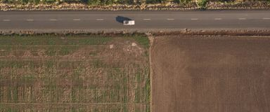 Вспаханное поле вдоль дороги, взгляд сверху стоковое изображение