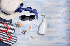Вспомогательное оборудование пляжа Шляпа, темповые сальто сальто и сливк на голубой деревянной предпосылке стоковое изображение