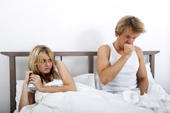 Вспугнутая женщина смотря человека кашляя в кровати стоковая фотография
