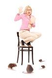 Вспугнутая женщина стоя на стуле во время нашествия крысы стоковые изображения rf