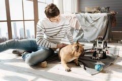 Вспугнутая собака вытаращить на роботе его мастера Стоковые Фото