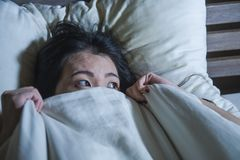 Вспугнутые детеныши и усилили азиатскую китайскую женщину лежа в кошмаре кровати страдая в страхе и панике схватывая одеяло покры стоковое изображение