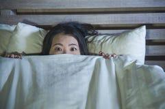 Вспугнутые детеныши и усилили азиатскую китайскую женщину лежа в кошмаре кровати страдая в страхе и панике схватывая одеяло покры стоковые изображения