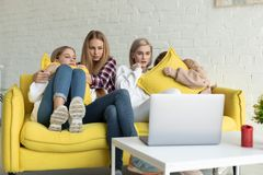 Вспугнутые молодые лесбосские пары с дочерьми в случайных одеждах сидя совместно на желтой софе дома, вышли из семьи стоковая фотография rf