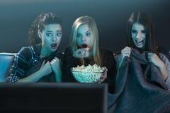 Вспугнутые подростковые смотря кино стоковая фотография